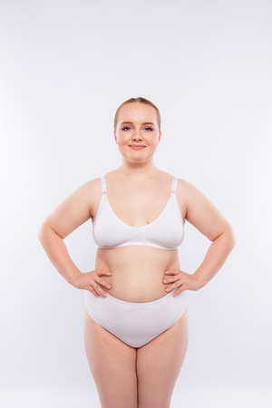 Vertical photo of fat model dressed in compression garments, she has sagged flawed skin with stretchmarks fat folds because of unhealthy nutrition bad metabolism, isolated on white background 免版税图像 - 97865235