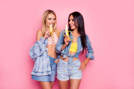 Beautiful attractive lovely careless charming flirty coquettish women clothed in denim stylish shirts, tops, shorts and skirt are fooling around and eating bananas, isolated on bright pink background