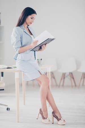 Pełna długość, widok z boku, profil pół twarzy uroczego, ładnego, miłego, uroczego finansisty opierającego się na biurku, trzymającego w rękach schowek