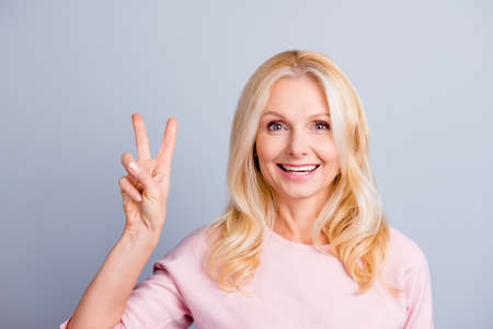 Close up portrait of pretty beautiful groomed gorgeous cute stunning granny making demonstrating v-sign with hand isolated on gray background copy-space Stock Photo