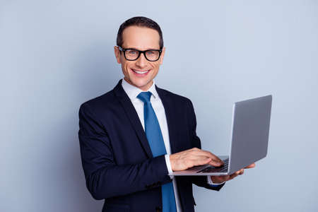 Portrait of smart exited cheerful satisfied financier using netbook isolated on gray background