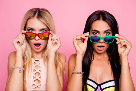 Pretty, charming, astonished, frustrated impressed, stressed, depressed ladies, tourists looking out glasses with wide open eyes and mouth, holding eyelets with hands, isolated on pink background Foto de archivo