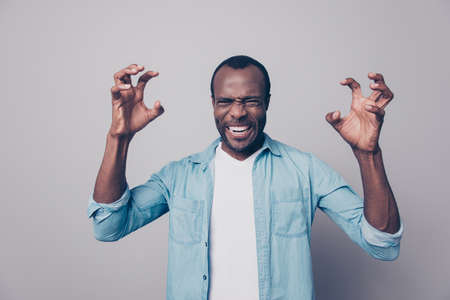 Portrait of nervous, angry, violent, out of himself, emotional man gesture with hands, looking at camera, isolated on grey background