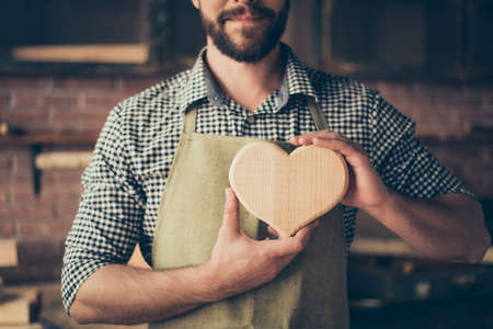 Cropped close up photo of happy cheerful joyful carpenter in love, he is showing a heart made of wood