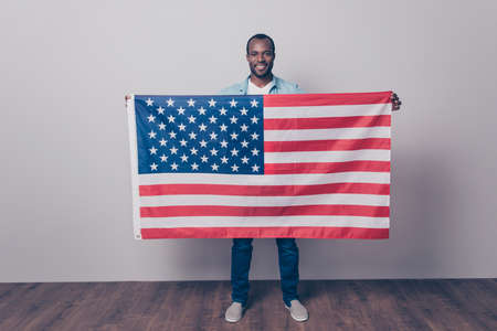 Full length portrait of cheerful glad joyful confident with beaming smile guy wearing denim casual outfit, holding flag of the USA in front of him, isolated on gray background