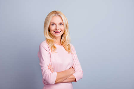 Portrait of excited cheerful beautiful confident middle-aged woman standing with crossed arms isolated gray background copy-space Stock Photo