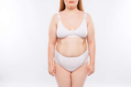 Cropped portrait of chubby fat curvy with excess weight young positive model with flaws on skin, isolated on white background