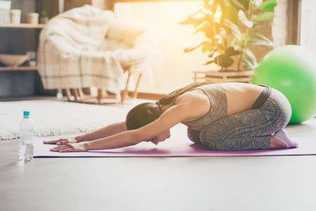Side profile view photo of concentrated confident beautiful attractive charming skinny muscular sportswoman sitting in yoga position on the floor in sun beams