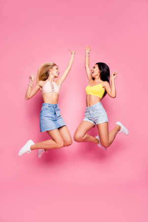 Attractive, comic, pretty sisters in casual outfit jumping with hands up, pink background
