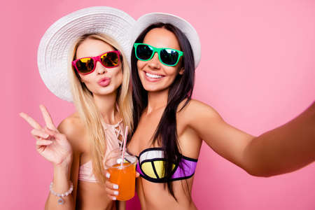 pretty tourists shooting selfie on front camera, showing two fingers with pout lips, having alcohol beverage, isolated on pink background