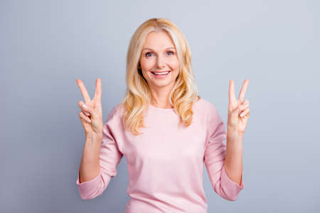 Portrait of cheerful excited friendly beautiful pretty cute lovely senior lady making v-signs isolated on gray background copy-space Stock Photo