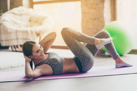 Side profile view photo of cheerful fresh delightful strong enduring slim beautiful attractive dressed in gray tight sportive top and pants girl doing core crunches on the purple mat at club Imagens