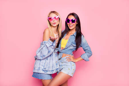 Beautiful playful cheerful women dressed in fashionable stylish shorts, shirt, jacket, top, funny star and heart glasses are embracing, sending air-kiss, isolated on bright pink background