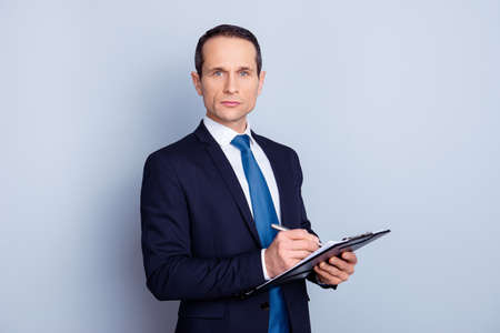 Portrait of focused clever intelligent concentrated representative with pencil and clipboard writing ideas checking work of staff manager in personnel department isolated on gray background copy-space