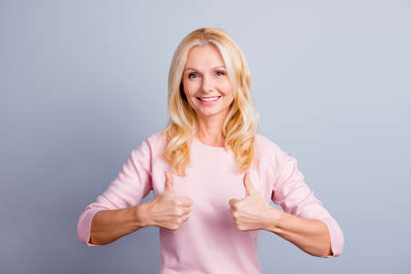 Portrait of cute dream dreamy lovely beautiful confident satisfied middle aged woman demonstrating thumb-up isolated on gray background