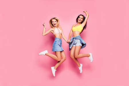 Beautiful attractive funny joyful cheerful relaxed carefree girls clothed in casual trendy outfit and white shoes are jumping up and holding hands, isolated on bright pink background Standard-Bild