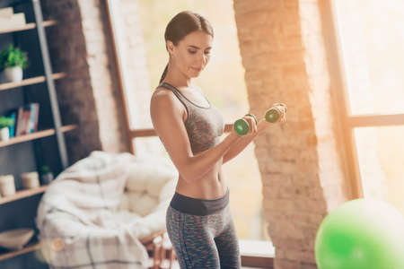 Side profile view photo of attractive powerful muscular woman holding green dumbbells in hands trying to built muscle mass at class Stockfoto