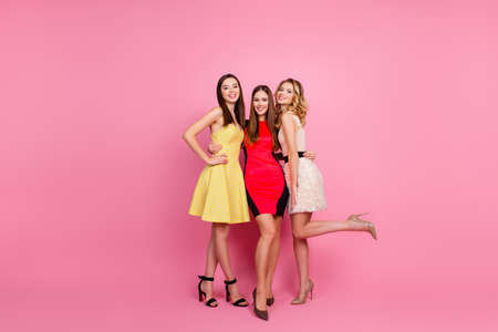 Full length portrait of three pretty girls, party time of stylish girls group in elegant dresses standing over pink background