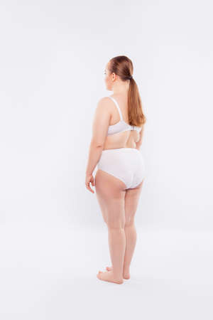 womans body with sagged flabby pigmented skin, dressed in white big-size underlinen, isolated on white background Stock Photo