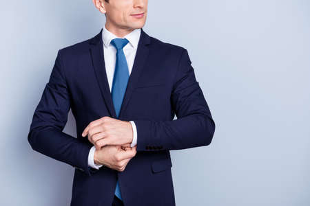 stylish man in formal wear, blue suit, fixing buttons on a cuff of white shirt, standing over gray background