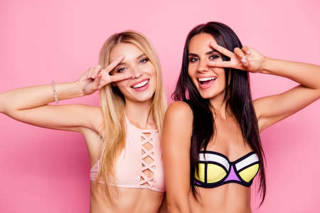 Close up portrait of happy beautiful attractive playful charming cute smiling women wearing swimsuit, are showing v-sign near their eyes, isolated on bright vivid pink background Stock fotó