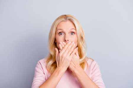 Close up portrait of funky curious cunning beautiful talkative gentle wondered astonished amazed lovely journalist grandmother grandma granny closes covers mouth isolated on gray background Banque d'images