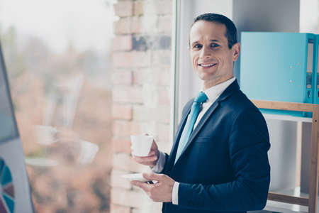 Portrait of entrepreneur wearing classic suit and shirt holding aromatic fresh cup of coffee waiting for client 스톡 콘텐츠