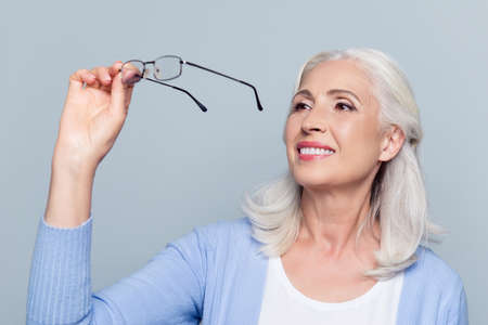 Old, charming, pretty woman looking through eyeglasses standing over grey background