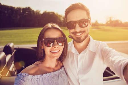 Romantic well dressed dreamy partners posing near transport, take shot, make memories of honeymoon Stockfoto