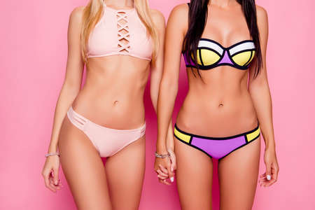 Cropped close up photo of beautiful attractive slim figured charming girlfriends bodies clothed in modern trendy fashionable bikini, they are holding hands, isolated on bright pink background