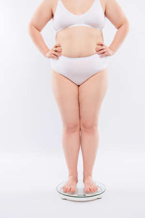 Cropped full-length full-size of fatty chubby with orange-peel flawed skin dressed in tight underwear standing on glassy scales, isolated on white background 免版税图像