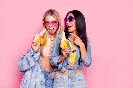 Beautiful attractive funny joyful cheerful women clothed in trendy outfit and star heart glasses are showing tongue and laughing isolated on pink background