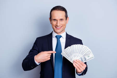 Portrait of glad handsome smart man adverting his deal holding money isolated on gray background