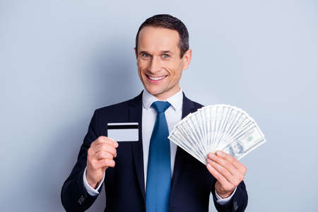 Close up portrait of confident excited joyful with toothy smile millionaire demonstrating pack of money plastic card isolated on gray background