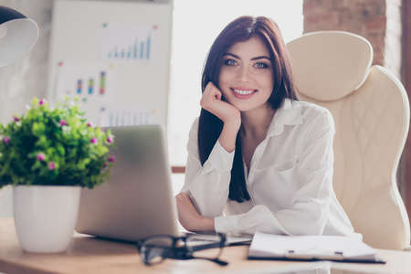 Close up portrait of beautiful confident pretty peaceful calm leaning on hand wearing white blouse entrepreneur sitting at table in modern light workstation