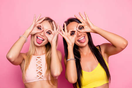 charming girls on holidays making binoculars with their fingers and showing tongue standing over pink background Stock Photo