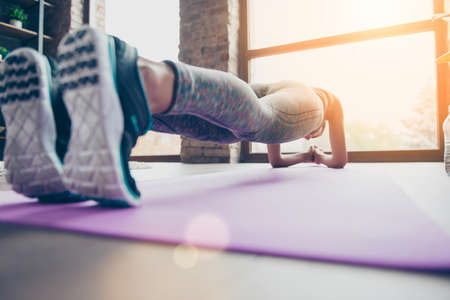 Close up photo of sportswomans sneakers. Athlete is holding plank position standing on elbows on purple carpet in class club gym view on window