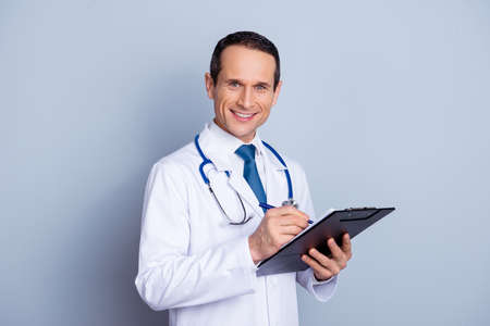 Portrait of glad experienced cheerful with toothy beaming shiny smile therapist making notes to his clipboard in hands writing prescription to his patient isolated on gray background