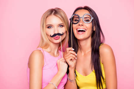 Close up portrait of two crazy funny cheerful comic attractive beautiful girlfriends wearing summer clothes and having fun using fake mustache and eyewear, isolated on bright pink background Фото со стока