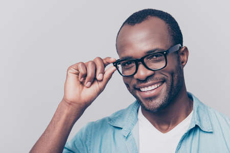 Portrait of positive, smiling, attractive guy with black skin beaming smile holding eyelet of glasses on his face with fingers, looking at camera, isolated on grey background