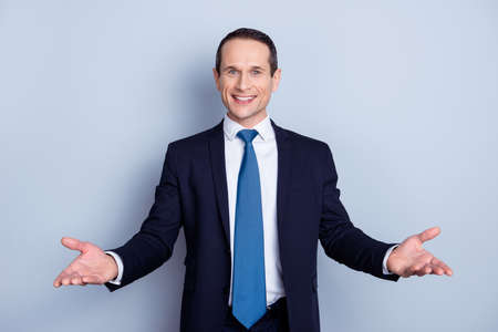 Cheerful, nice man in formal wear with tie having his hands open like hospitable gesture, you are welcome, well met, standing over gray background