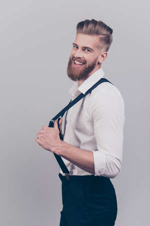 Vertical side profile half-turned portrait of cheerful excited careless classy rich confident laughing stylish careless guy correcting fixing his braces suspenders isolated on gray background