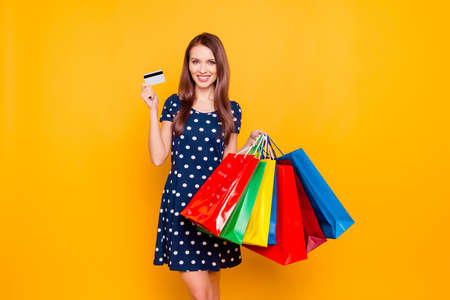 Charming pretty attractive sexy girl showing credit card and holding many colorful packages in hand, it is comfortable to use bank card for shopping, standing over yellow background