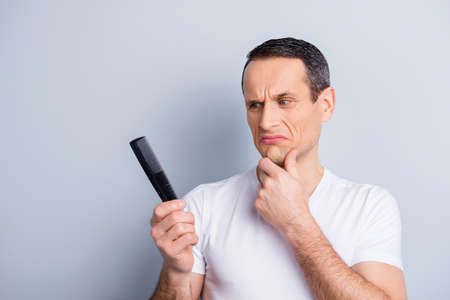 Portrait of shaved, trendy, experienced, brunet, neat man touching his chin with hand looking at comb in his hand with disgust expression, isolated on grey background
