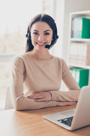 Support waiting service modern technology concept. Vertical portrait of cheerful joyful expert experienced qualified smart attractive excited receptionist sitting at the table desktop near netbook Stock fotó