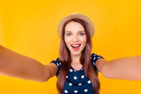 Self portrait of nice, amazing, pretty, positive, laughing, glad woman shooting selfie in two hands on front camera,  having polka-dot outfit, isolated on yellow background Stock Photo