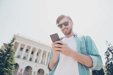 Low-angle portrait of cheerful satisfied handsome attractive with toothy beaming smile shiny careless excited confident manager entrepreneur using smartphone for communication holding in hands