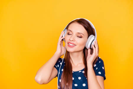 Portrait of pretty, charming, nice woman with headphones on her head, listen to music, enjoying her favorite song with closed eyes, holding hands on headset , isolated on yellow background Stock Photo