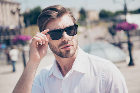 Close up portrait of handsome attractive smart stylish serious concentrated thinking focused pensive pondering with modern hairdo financier banker model fixing correcting eyewear city on background