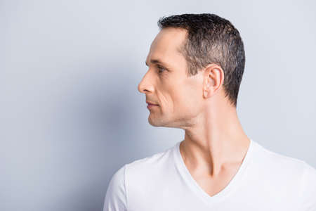 Portrait with copy space, empty place for product, advertisement of attractive, stylish man with turned profile face to the side, having perfect ideal oiled, dry skin, isolated on grey background Stockfoto